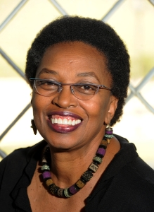Smiling woman wearing glasses, black top, and purple and green beaded necklace and earrings.