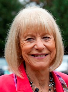 Smiling woman with short, white hair. She wears a pink jacket.